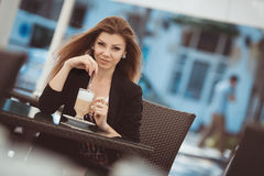 Portrait of beautiful smiling woman sitting in a cafe with laptop outdoor Royalty Free Stock Images