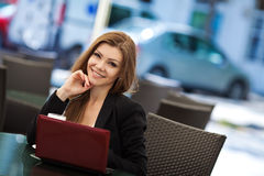 Portrait of beautiful smiling woman sitting in a cafe with laptop outdoor Royalty Free Stock Photos
