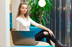 Portrait of beautiful smiling woman sitting on a comfortable chair in a cafe with black laptop. Pretty student doing work with lap Stock Photo
