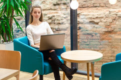 Portrait of beautiful smiling woman sitting on a comfortable chair in a cafe with black laptop. Pretty student doing work with lap Royalty Free Stock Photography