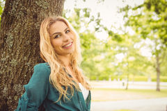 Portrait of beautiful smiling woman standing by tree Stock Image
