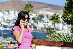 Portrait of beautiful smiling  woman talking on the phone outdoor on a sea background Royalty Free Stock Photo