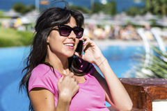 Portrait of beautiful smiling  woman talking on the phone outdoor on a sea background Stock Photo