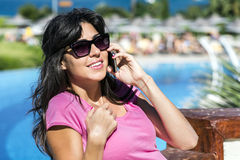 Portrait of beautiful smiling  woman talking on the phone outdoor on a sea background Stock Images