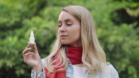 Portrait of beautiful smiling woman wearing red scarf holding allergic nose spray in her hand standing in the city park. Health care concept. Medicine stock video footage