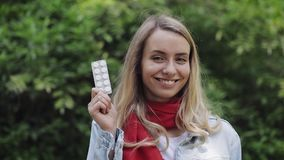 Portrait of beautiful smiling woman wearing red scarf holding blisterpack with pills in her hand standing in the city. Park. The girl winking eye. Health Care stock footage