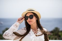 Portrait of a beautiful smiling young woman wearing straw hat and sunglasses while standing outdoor. Portrait of a beautiful smiling woman wearing straw hat and stock photography