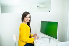 Portrait of a beautiful smiling woman, working at the computer with green screen, in an office environment.  royalty free stock images