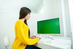 Portrait of a beautiful smiling woman, working at the computer with green screen, in an office environment.  royalty free stock photo