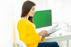 Portrait of a beautiful smiling woman working on her desk with green screen, in an office environment.  stock photos