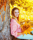 Portrait beautiful smiling woman with yellow maple leafs sitting under tree in sunny autumn Royalty Free Stock Photos