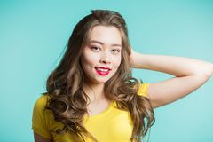 Portrait of a beautiful smiling woman in yellow t-shirt and red lips on a blue background. Closeup, horizontal, copys pace. Expressive facial expressions Stock Image