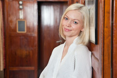 Portrait of beautiful smiling young blond woman. Resting her head against photo frame Stock Photo