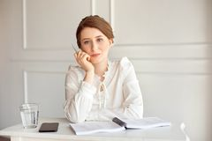 Portrait of a beautiful smiling young brunette businesswoman in a white shirt sitting on a bright modern workstation stock images
