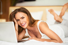 Portrait beautiful smiling young brunette woman laying in bed relaxing using laptop computer. Smiling beautiful woman lying down on bed Stock Images