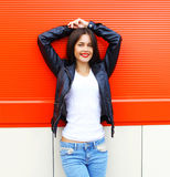 Portrait beautiful smiling young brunette woman wearing a rock black leather jacket and jeans posing in city Royalty Free Stock Photos
