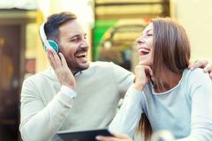 Portrait of beautiful smiling young couple sitting in cafe using tablet. And listening to music Royalty Free Stock Image