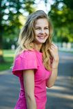 Portrait of a beautiful smiling young cute girl in a pink summer dress. Portrait of a beautiful smiling young girl in a pink summer dress Royalty Free Stock Image