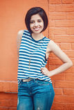 Portrait of beautiful smiling young hipster latin hispanic girl woman with short hair bob. In blue jeans, striped tshirt, leaning on red brick wall in city Royalty Free Stock Image