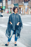 Portrait of beautiful smiling young hipster latin hispanic girl woman with short hair bob. In torn jeans, grey blue poncho cape, standing outside in city royalty free stock image