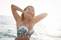 Portrait of a beautiful smiling young woman in bikini on the beach. Female model posing in swimsuit on sea shore. Summer holidays royalty free stock photo