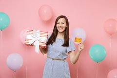 Portrait of beautiful smiling young woman in blue dress holding credit card and red box with gift present on pink. Background with colorful air balloon royalty free stock images