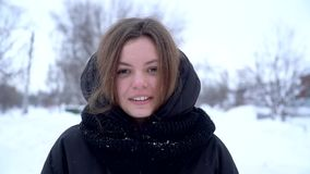 Portrait of beautiful smiling young woman outside enjoying winter in black clothes happy skincare concept slow motion. Portrait of beautiful smiling young woman stock video footage