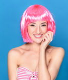 Portrait of beautiful smiling young woman with pink hair on a blue background Royalty Free Stock Photography