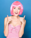 Portrait of beautiful smiling young woman with pink hair on a blue background Stock Photography