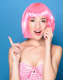 Portrait of beautiful smiling young woman with pink hair on a blue background Stock Image