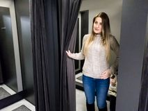 Portrait of beautiful smiling young woman trying on warm wool sweater in shopping mall dressing room royalty free stock photo