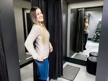 Portrait of beautiful smiling young woman trying on warm wool sweater in shopping mall dressing room royalty free stock photography