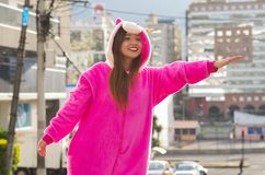 Portrait of a beautiful smiling young woman wearing a pink unicorn costume, taking a taxi in outdoors of the city of Stock Photo