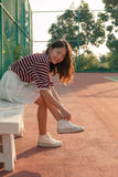 Portrait of beautiful sport girl sitting in tennis courts looking Royalty Free Stock Image