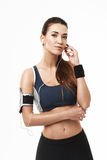 Portrait of beautiful sportive girl in headphones and sportswear posing looking at camera over white background. Copy space Stock Image