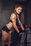 Portrait of a beautiful sporty muscular girl in the gym stock images