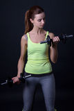 Portrait of beautiful sporty woman with dumbbells over grey Stock Images