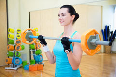 Portrait of beautiful sporty woman exercising with barbell in gy Royalty Free Stock Photography