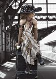 Portrait of a beautiful steampunk dressed woman in traditional clothing traveling with a suitcase waiting for the train. stock photos