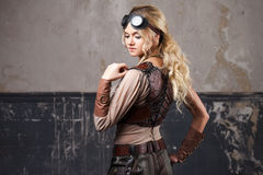 Portrait of a beautiful steampunk woman in Aviator glasses over grey background. Stock Photos