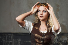 Portrait of a beautiful steampunk woman in Aviator glasses over grey background. Looking up Stock Images