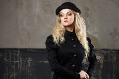 Portrait of a beautiful steampunk woman hat-bowler hat over grunge background. Royalty Free Stock Photos