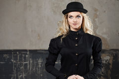 Portrait of a beautiful steampunk woman hat-bowler hat over grunge background. Royalty Free Stock Photography