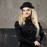 Portrait of a beautiful steampunk woman hat-bowler hat over grunge background. Stock Photos