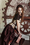 Portrait of a beautiful steampunk woman. Near big clock Stock Image