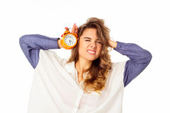 Portrait of a beautiful stressed woman holding clock in hands Stock Images