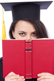 Portrait of a beautiful student in graduation gown  holding a bo Stock Image