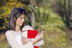 Portrait of a beautiful student woman sending messages  in the park. Portrait of a beautiful  woman with book and wallet in the hands ,talking on the phone Royalty Free Stock Photos