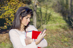Portrait of a beautiful student woman sending messages  in the park. Portrait of a beautiful  woman with book and wallet in the hands ,talking on the phone Royalty Free Stock Image