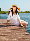 Beautiful stylish brunette woman on a pier Stock Image